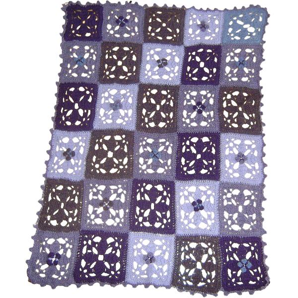 Dette tæppe er hæklet af 30 tern i 5 forskellige lilla nuancer. Tæppet er hæklet i alpacagarn. Størrelse: længde : 80cm     bredde : 60cm De små blomster hækles til sidst og sys på.